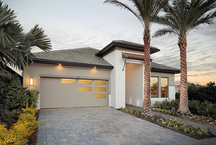 Clopay Modern Steel Collection garage door, grooved panel design with custom window layout. Narrow reed decorative glass. Desert tan paint. Double car